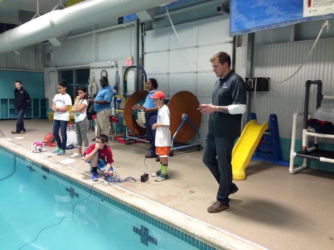 Students stand on side of pool as they control their SeaPerch robots using a remots control.