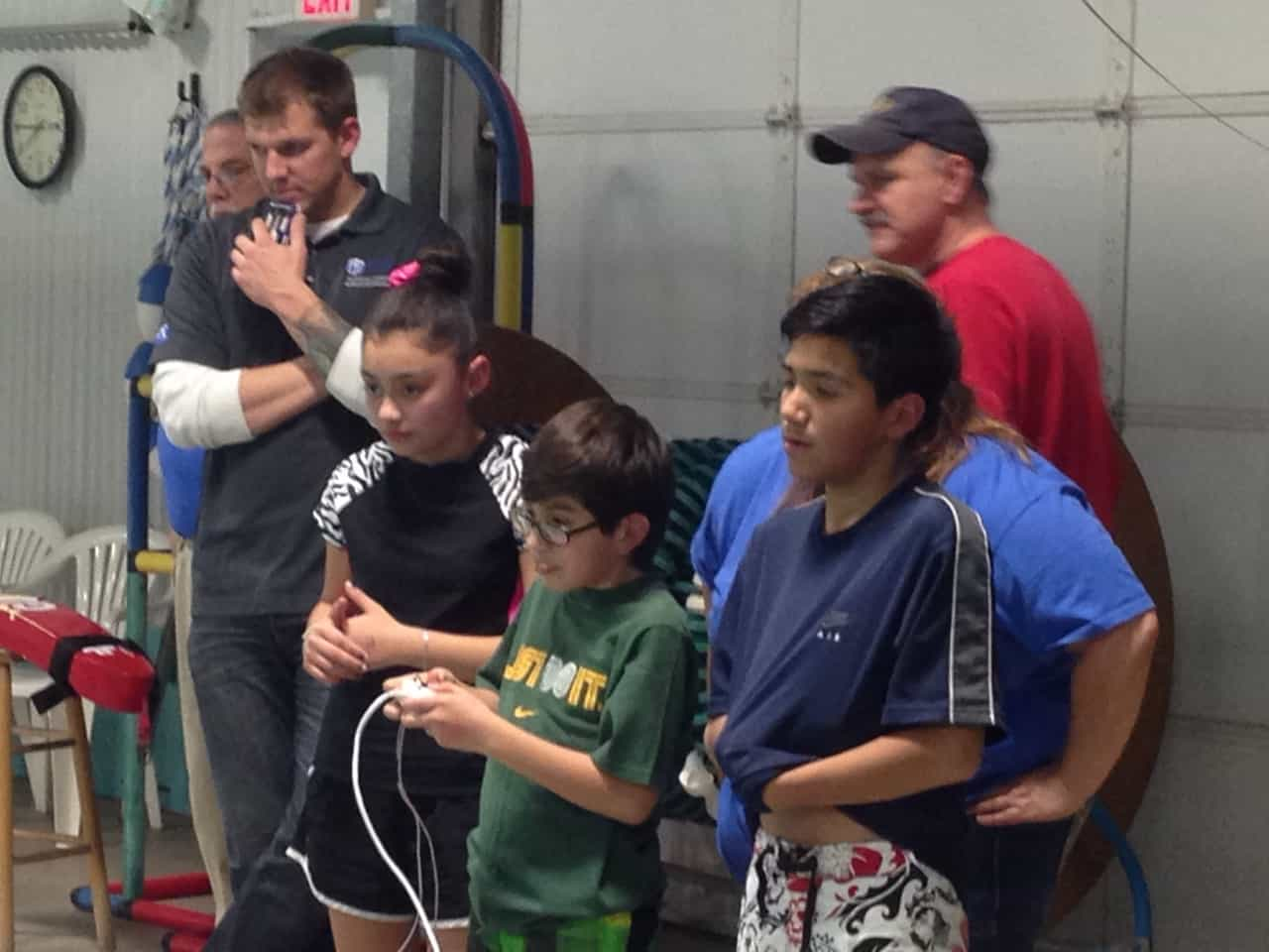 Kids watch as student uses controller to compete with SeaPerch robot