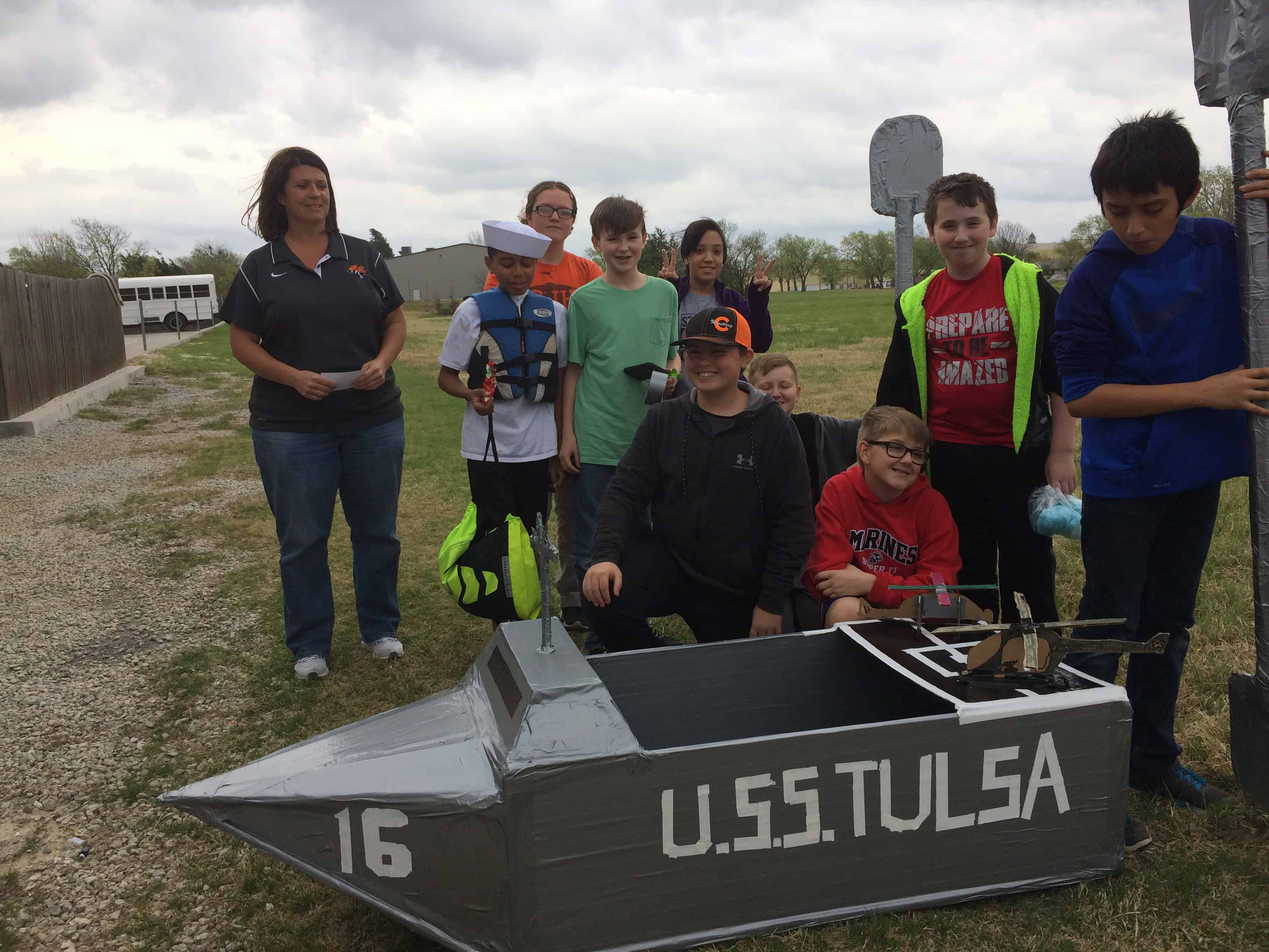Students pose with their replica of the U.S.S. Tulsa in the 2017 Cardboard and Duct Tape Boat Regatta