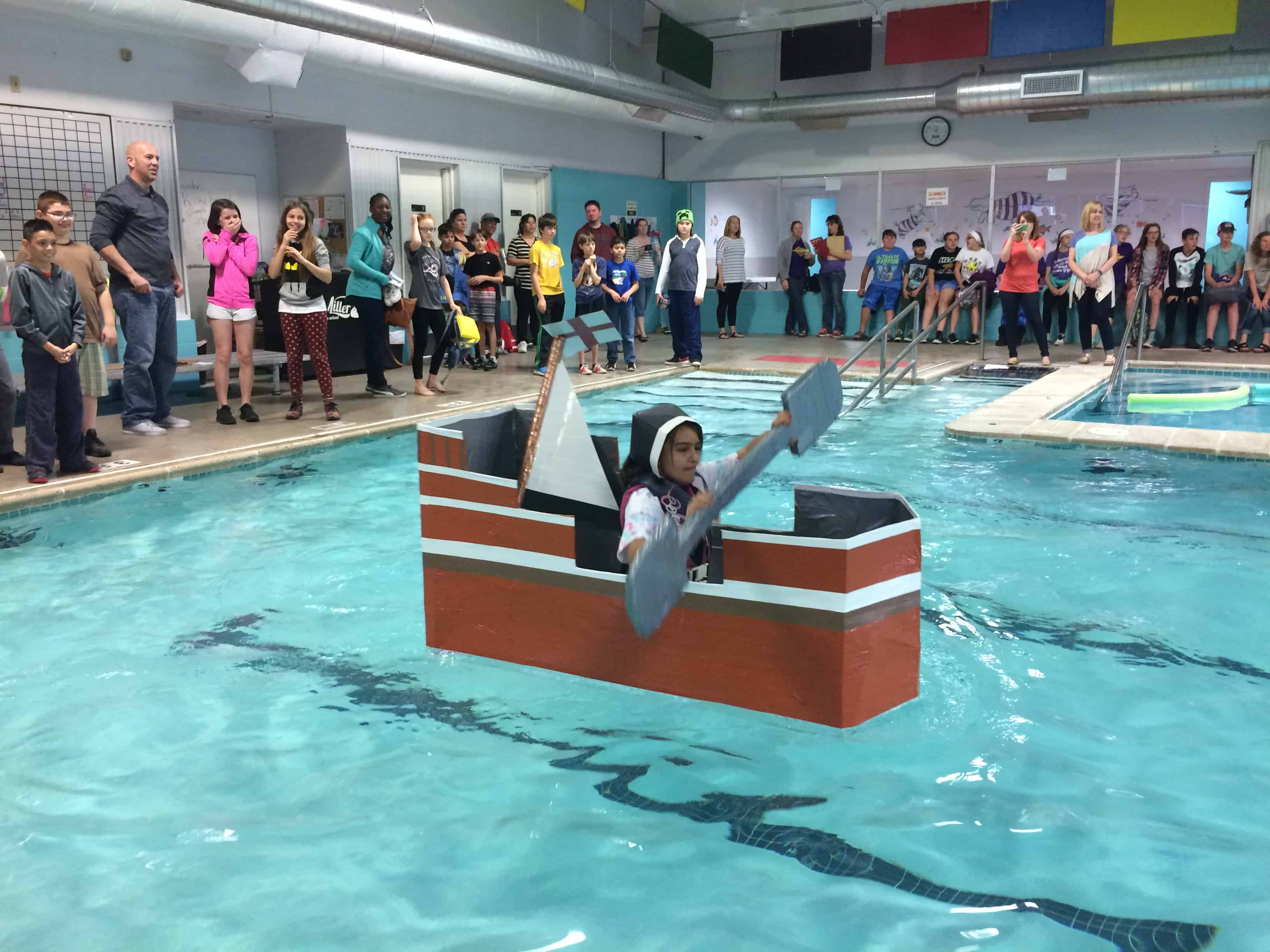 Student in costume paddles her boat in the 2017 Cardboard and Duct Tape Boat Regatta