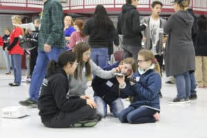 Four girls sit on ground at Tulsa Tech Riverside Campus hanger to inspect their drone during the 2019 Flight Night Drone Competition