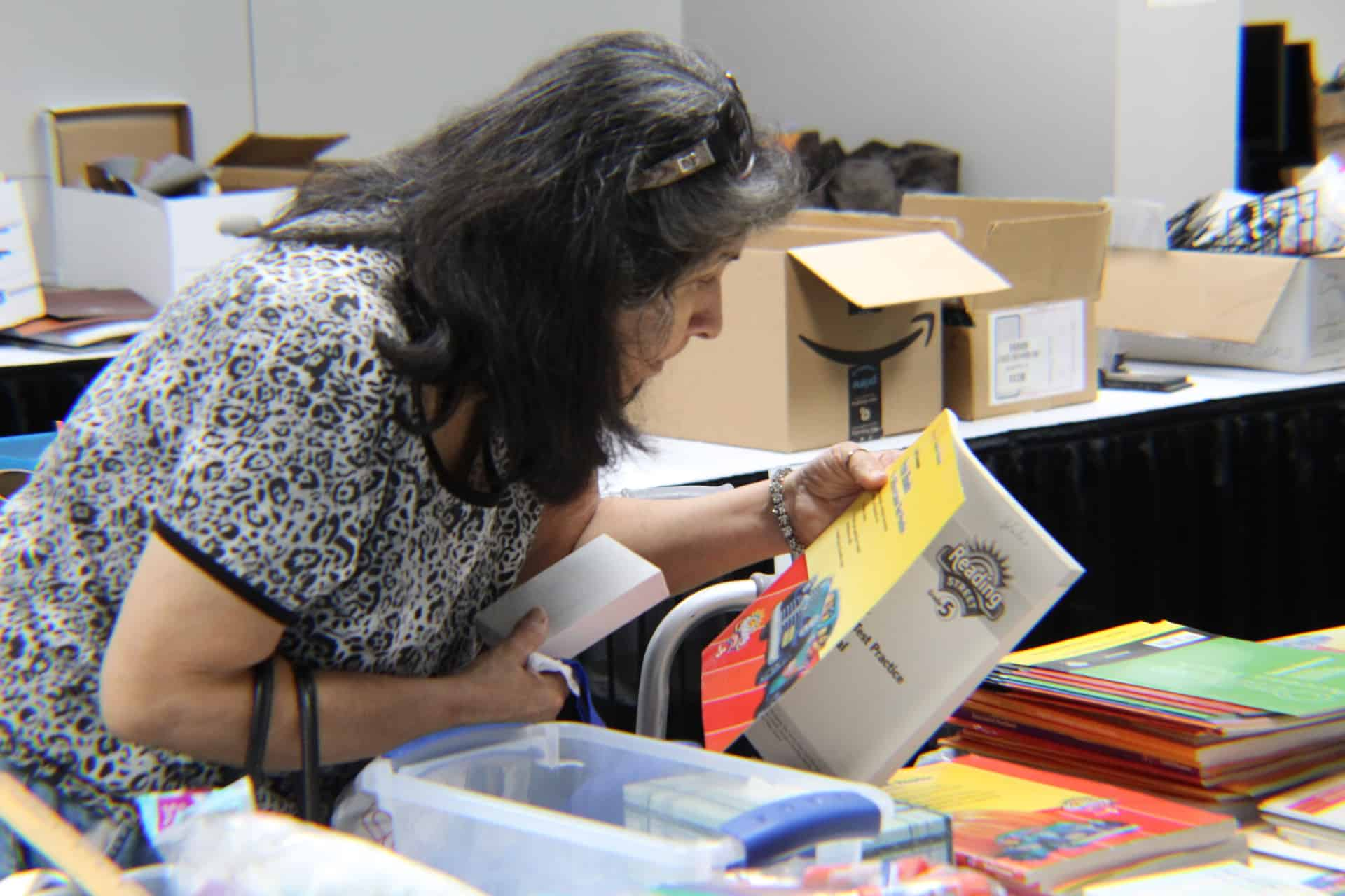 A teacher inspects a free book at the STEM Shoppe Open House.