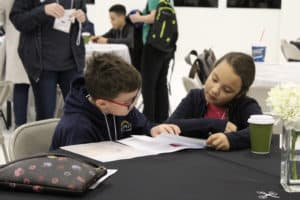 A young boy and girl review their research while sitting at a table during the 2019 TCC Take-Off