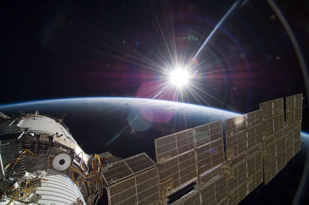 The International Space Station sits in the bottom left corner. In the background, the sun shines over earth.