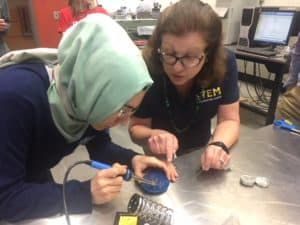 USNA STEM Center representative leads educator through soldering of SeaPerch robot