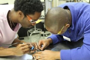 Two teachers solder a SeaPerch robot