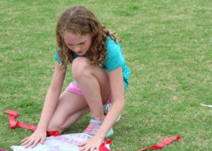Girl spreads out kite to fix it on the grass